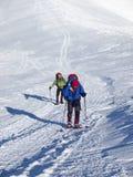 Männer in den Schneeschuhen gehen in die Berge Lizenzfreie Stockbilder