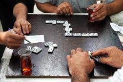 Männer in den Teehäusern trinken Tee- und Spieldominos stockfotografie