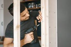 Männer in der grauen Kleidung arbeiten als Schraubenzieher und befestigen einen Holzrahmen für das Fenster am Gipsfasergipsplatte stockbild