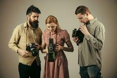 Männer in der karierten Kleidung, Retrostil Firma von beschäftigten Fotografen mit alten Kameras, Schmierfilmbildung, Funktion Mä lizenzfreie stockfotos