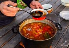 Männer, der Koch gießt eine Schaufel der Suppe vom Topf in eine Kranschüssel lizenzfreie stockbilder