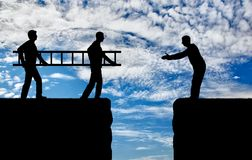 Männer des Schattenbildes zwei tragen eine Leiter, um den Übergang zu ebnen der Abgrund für einen anderen Mann Stockfoto