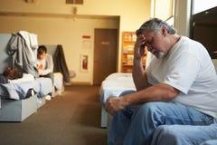 Männer, die auf Betten im Obdachlosenasyl liegen stockbild