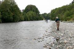 Männer, die auf den Banken von Fluss fischen Stockfotos