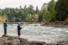 Männer, die auf der Flussbank fischen Stockbilder