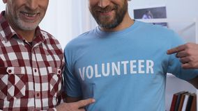 Männer, die auf freiwilligen Text auf T-Shirt, freie Hilfe zu den Leuten im Bedarf zeigen stock footage