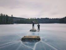 Männer, die auf gefrorenem See stehen stockfotografie