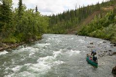 Männer, die auf schnellem Abenteuer des Kanus in Alaska auslösen lizenzfreies stockbild