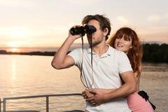 Männer, die binocularus untersuchen, während sein Mädchen ihn umarmt stockbilder