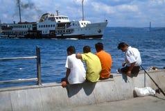 Männer, die Boote fischen und aufpassen. Istanbul, die Türkei lizenzfreies stockfoto