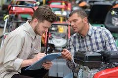 Männer, die Brennstoff angetriebenen Aufsitzmäher reparieren stockbild