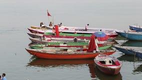 Männer, die an bunten Booten in der Bucht vom Ganges in Varanasi arbeiten stock footage