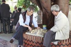 Männer, die chinesisches Schach durch die Straße spielen Lizenzfreie Stockfotos