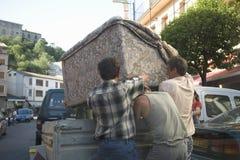 Männer, die Couch in Ainsa, Huesca, Spanien in Pyrenäen-Bergen bewegen Lizenzfreie Stockfotos