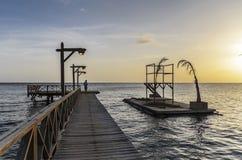 Männer, die in einem langen hölzernen Fischenpier bei Sonnenuntergang aufwecken lizenzfreies stockbild