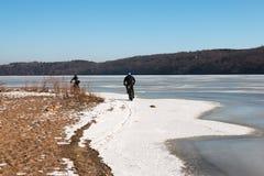 Männer, die Fettfahrräder entlang gefrorenem Fluss Mississipi reiten Stockfotografie