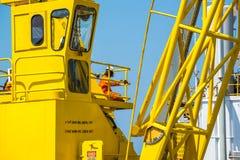 Männer, die am gelben Kran mit blauem Himmel arbeiten Lizenzfreies Stockbild