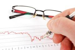 Männer, die Geschäftsdiagramm mit Gläsern im Hintergrund analysieren Stockbild