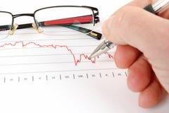 Männer, die Geschäftsdiagramm mit Gläsern im Hintergrund analysieren Lizenzfreies Stockfoto