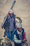 Männer, die Kerzen und verschiedene religiöse Einzelteile in Nepal führen Lizenzfreie Stockfotos