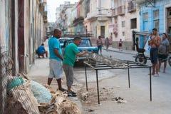 Männer, die Matratzen auf kubanischer Straße abstreifen Stockfoto