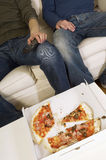 Männer, die Mit halb aufgegessener Pizza auf Tabelle fernsehen Lizenzfreie Stockfotos