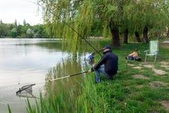 Männer, die mit Stange auf dem See im Frühjahr fischen Lizenzfreie Stockbilder