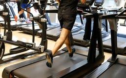 Männer, die sein Training an der Turnhalle auf laufenden Maschinen tun stockfoto
