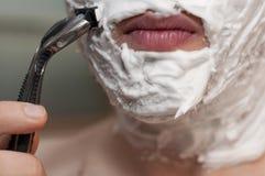 Männer, die seinen Bart mit Schaumgummi und Rasiermesser rasieren stockfoto