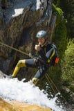 Männer, die Wasserfall absteigen Stockfotos