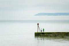 Männer, die weg von der Buhne im ruhigen See fischen Stockbild