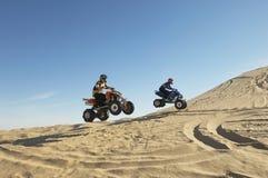 Männer, die Wheelies auf Viererkabel-Fahrrädern tun Stockfoto