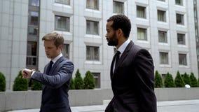 Männer, die zum wichtigen Geschäftstreffen, Uhr betrachtend, Zeitmanagement gehen lizenzfreies stockbild