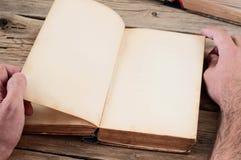 Männer dreht die Seite des Buches auf dem Holztisch Stockbilder
