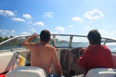 Männer in einem Bewegungsboot Stockbild