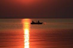 Männer in einem Boot am Sonnenuntergang Lizenzfreies Stockfoto