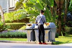 Männer entleeren Plastikflaschen, die Abfall in Abfalleimer seitlich am Weg an der Gartenöffentlichkeit aufbereiten Stockfotografie