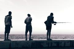 Männer fischen entlang dem Malecon in Havana, Kuba stockbilder