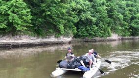 Männer gehen mit dem Fluss in ein Boot stock video footage