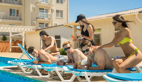 Männer genießen eine Massage von den Frauen nahe dem Swimmingpool Lizenzfreie Stockfotos
