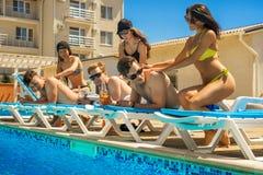 Männer genießen eine Massage von den Frauen nahe dem Swimmingpool Lizenzfreies Stockbild