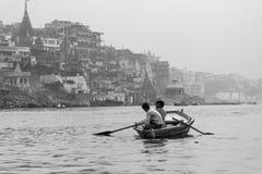 Männer im Reihenboot in Varanasi, Indien Stockbilder