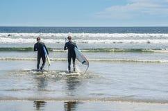 Männer im Wetsuit, der geht zu surfen Lizenzfreie Stockfotos