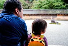 Männer Kyotos Japan und kleines Mädchen sitzen auf dem berühmten Steingarten in Kyoto Rückseitige Ansicht stockbild