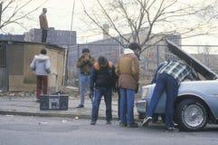Männer mit dem Hochkonjunkturkasten, der Auto repariert stockfotos