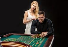 Männer mit den Frauen, die Roulette am Kasino spielen lizenzfreie stockbilder