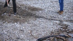 Männer mit einer Schaufel graben einen Graben auf dem Strand stock footage