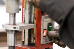 Männer mit Handschuhen schalten An-/Aus-Schalter auf Bohrmaschine ein stockfotos