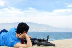 Männer mit seinem Fahrrad, das auf einem Strand liegt Lizenzfreies Stockfoto