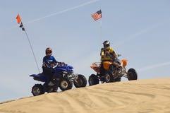 Männer mit Viererkabel-Fahrrädern auf Sanddüne Lizenzfreies Stockfoto